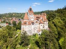 Klislott på en kulle med höga tornspiror, väggar, röda belade med tegel tak, arkivfoton