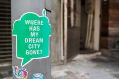 Klistermärke på en Hong Kong lampost somfrågar ` var har min dröm- stad väck? `, Royaltyfri Bild