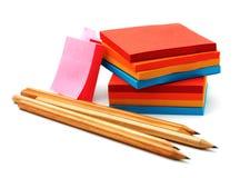 Klistermärkear och blyertspennor som isoleras på en vit Arkivfoto