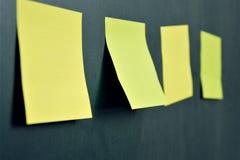 Klistermärkear på svart tavla en i fokus arkivbild