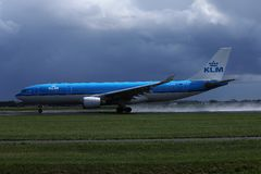 KLM aircraft landing on Amsterdam Schiphol Airport, AMS. KLM Royal Dutch Airlines jet landing on Schiphol Airport, AMS, Netherlands. Cloudy royalty free stock images