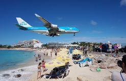 A KLM Boeing 747 lands over Maho Beach in St Martin. SAINT MARTIN, DUTCH ANTILLES --30 NOVEMBER 2014-- The beach at Maho Bay is one of the world's premier Royalty Free Stock Image