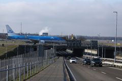 KLM plane taxiing over bridge in Schiphol Airport, AMS Amsterdam, close-up view. KLM jet doing taxi on a bridge in Schiphol Airport, AMS Amsterdam, close-up view stock photo