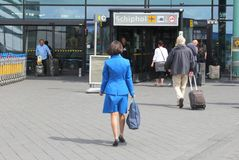 KLM stewardess goes working at Amsterdam Schiphol Airport, Netherlands   Royalty Free Stock Photography