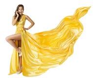 Klänning för kvinnaskönhetmode, härlig flicka i den gula fladdrakappan för flyg som står på höga häl för ett ben, vinka för tygto Royaltyfri Foto