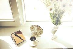 Klocka, anteckningsbok, kaffe och blomma Royaltyfria Bilder