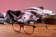 Klocka, exponeringsglas och en skjorta på en trätabell Arkivbild