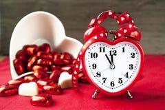 Klocka för förälskelse för valentinförälskelse hjärta formad röd med söta choklader Arkivbild