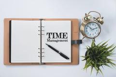 Klocka för guld- klocka, grön växt och mellanrumsanteckningsbok med ord för TID LEDNING på den lekmanna- vitlägenheten Royaltyfri Fotografi