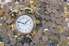 Klocka för guld- klocka på en grupp av mynt Royaltyfri Fotografi