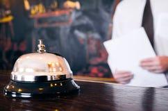 Klocka för hotellmottagandeservice med portvakten som rymmer en mapp royaltyfri foto