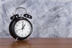 1 klocka för tappning för nolla-`-klocka på wood tabell- och väggbakgrund Royaltyfri Foto
