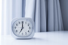 Klocka för vit fyrkant på den vita sängställningen med vit gardinbakgrund, morgontid i minsta stilgarnering Arkivfoto