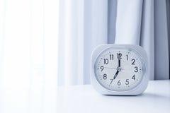 Klocka för vit fyrkant på den vita sängställningen med vit gardinbakgrund, morgontid i minsta stilgarnering arkivbilder