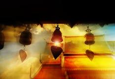Klocka i dunkelt ljus och linsen blossar i tempel- och himmelbakgrund Arkivbilder