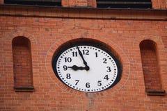 Klocka i ett tegelstenhus Arkivfoto