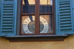 Klocka i fönster arkivbild