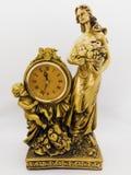 Klocka, kvinna rymmer en fruktkorg, och pys för bronsskrivbord som arkivbilder