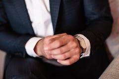 Klocka med den vita visartavlan på handen av en man i en vit skjorta Arkivbild
