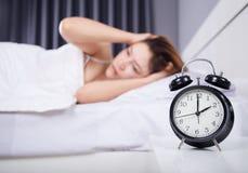 Klocka med kvinnan som är sömnlös på säng Fotografering för Bildbyråer