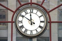Klocka med roman tal på glasväggen Arkivfoto