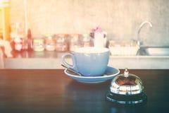 Klocka och den varma kaffekoppen på coffee shop kontrar för varning eller wark upp begrepp Royaltyfri Fotografi