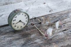 Klocka och exponeringsglas på en tabell Arkivbilder