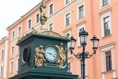 Klocka och lampa i gator av St Petersburg, Ryssland arkivbilder