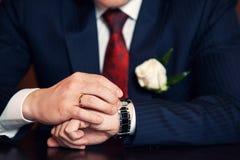 Klocka på brudgummens hand Arkivbild