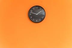Klocka på den orange väggen Arkivbild