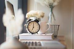 Klocka på kontorsskrivbordet Arkivbild