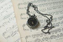 Klocka på musikaliska anmärkningar Arkivbilder
