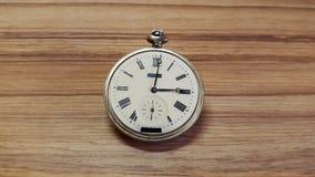 Klocka på wood bakgrund Royaltyfria Bilder