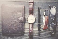 Klocka, plånbok, penna och exponeringsglas Arkivfoton