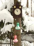 Klocka som dekoreras med julleksaker i vinterskogen på en gran som täckas med snö royaltyfri bild