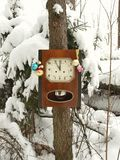 Klocka som dekoreras med julleksaker i vinterskogen på en gran som täckas med snö arkivbild