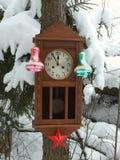 Klocka som dekoreras med julleksaker i vinterskogen på en gran som täckas med snö royaltyfri fotografi
