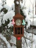 Klocka som dekoreras med julleksaker i vinterskogen på en gran som täckas med snö royaltyfria foton
