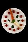 Klocka som göras av grönsaker på en vit platta- och svartbakgrund Royaltyfria Foton