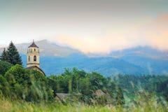 Klocka torn av det kyrkliga Sanet Giovanni i byn av Sassello Royaltyfri Bild