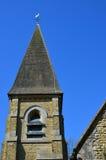 Klocka torn och tornspira på en engelsk kyrka Arkivbilder