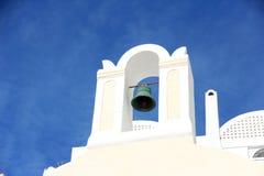 Klocka vit byggnad i Santorini Arkivbilder