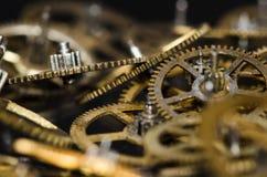 Klockadelar: Samling av metalliska klockakugghjul för tappning på en svart yttersida Arkivfoto