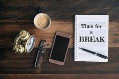 Klockan exponeringsglas, telefonen, kaffe, rånar och anteckningsboken med TIME FÖR ett AVBROTTSord royaltyfria bilder