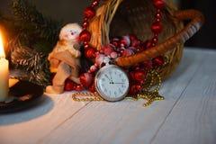 Klockan för stillebentappningfacket på bakgrunden av julprydnader, brännande stearinljus och gran förgrena sig Arkivfoto