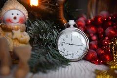 Klockan för stillebentappningfacket på bakgrunden av julprydnader, brännande stearinljus och gran förgrena sig Arkivbild