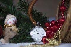 Klockan för stillebentappningfacket på bakgrunden av julprydnader, brännande stearinljus och gran förgrena sig Arkivfoton