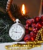 Klockan för stillebentappningfacket på bakgrunden av julprydnader, brännande stearinljus och gran förgrena sig Royaltyfria Bilder