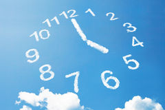 5 klockan i molnstil på blå himmel Arkivfoton