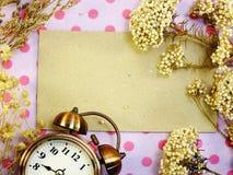 Klockan med utrymmebackgroun med den torkade blomman dekorerar Royaltyfria Foton